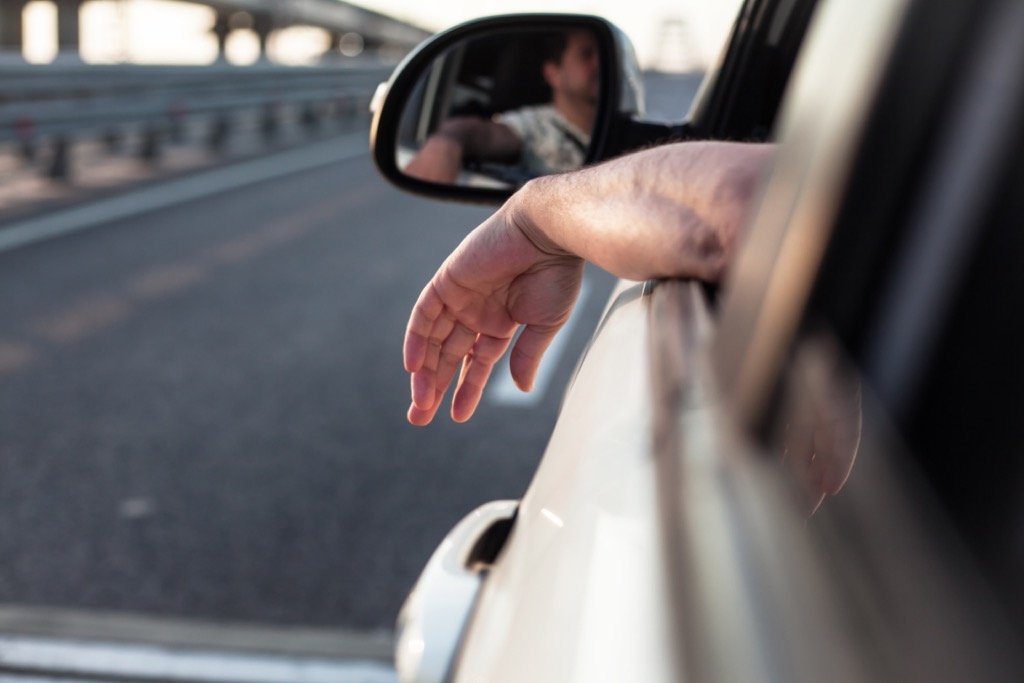 man-driving-with-arm-outside-car-window
